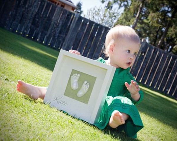 Little girl sitting in her backyard with the little feet Memory Castings Shadowbox she made as a newborn baby